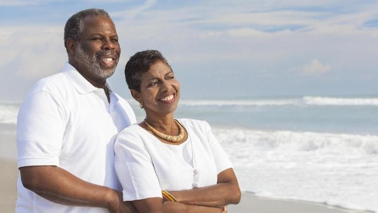 Older man and woman smiling on beach | 21401 Dentist