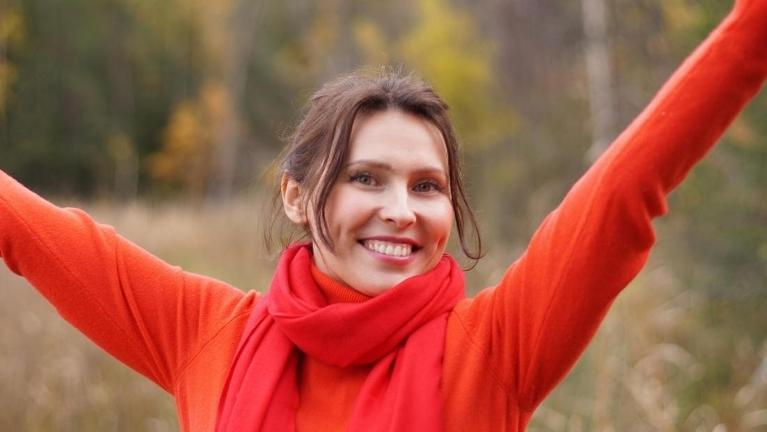 brown haired woman in a red sweater beaming against an autumn background